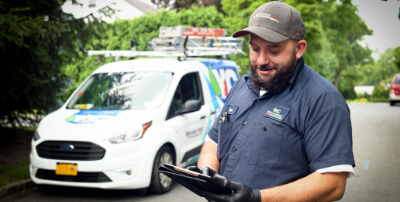 A technician reviewing a clipboard in front of a truck.